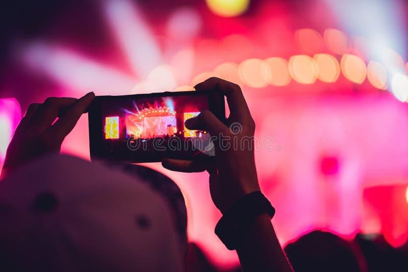 Leute, die Rockkonzert genießen und Fotos mit Handy a machen stockbilder