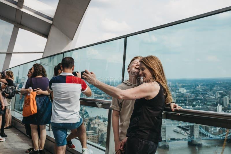 Leute, die selfies auf einem Freilichtbalkon im Himmel-Garten, London, Großbritannien nehmen stockbilder