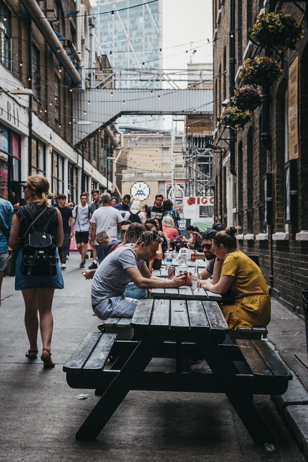 Leute, die Straßennahrung in Elys Yard, London, Großbritannien genießen lizenzfreie stockfotografie