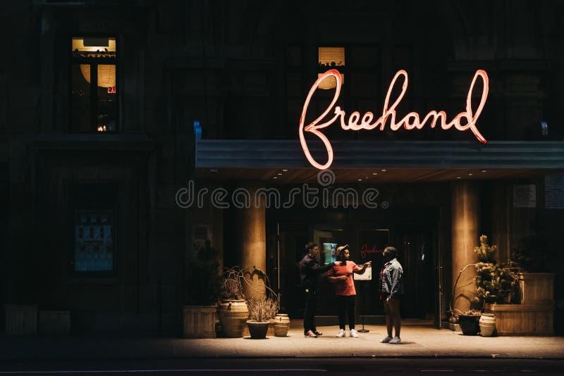 Leute, die unter dem Leuchtzeichen des freihändigen Hotels in F sprechen lizenzfreie stockfotografie