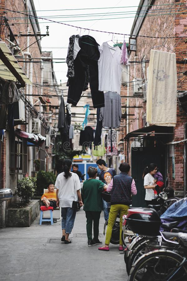 Leute, die vor ihrem Haus mit dem Trocknen von Kleidung sprechen lizenzfreies stockbild