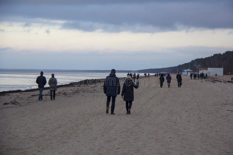 Leute, die während des Sonnenuntergangs bei Sandy Beach der Ostsee gehen stockfotografie