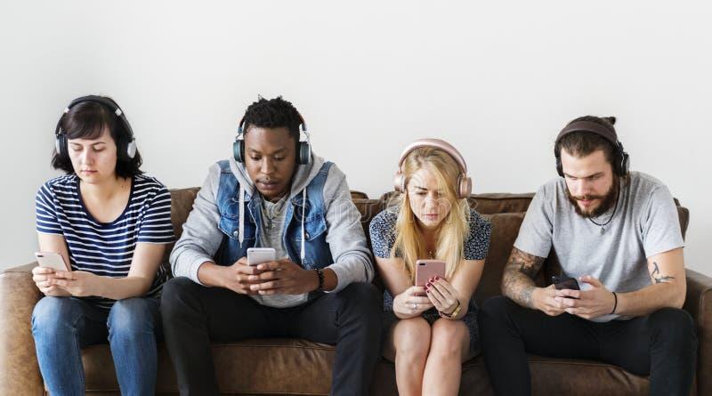 Leute, die zusammen Musik auf Couch genießen lizenzfreies stockbild