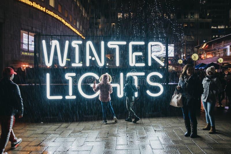 Leute durch das Zeichen an den Winter-Lichtern, Canary Wharf, London, Großbritannien stockfotos