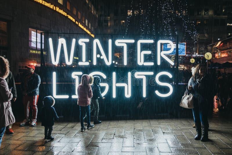 Leute durch das Zeichen an den Winter-Lichtern, Canary Wharf, London, Großbritannien lizenzfreie stockfotografie