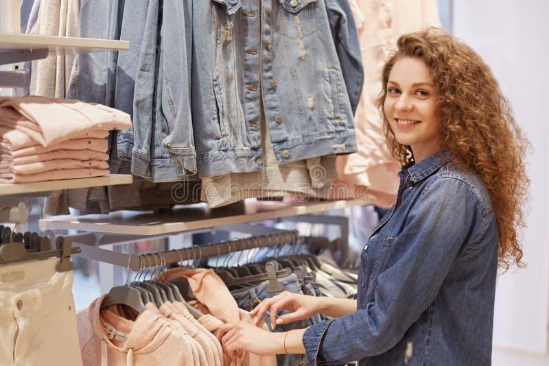 Leute-, Einkaufs-, Art-, Mode- und Verkaufskonzept Glückliche schöne junge Frau mit dem gelockten Haar, gekleidet in der Denimjac stockbild
