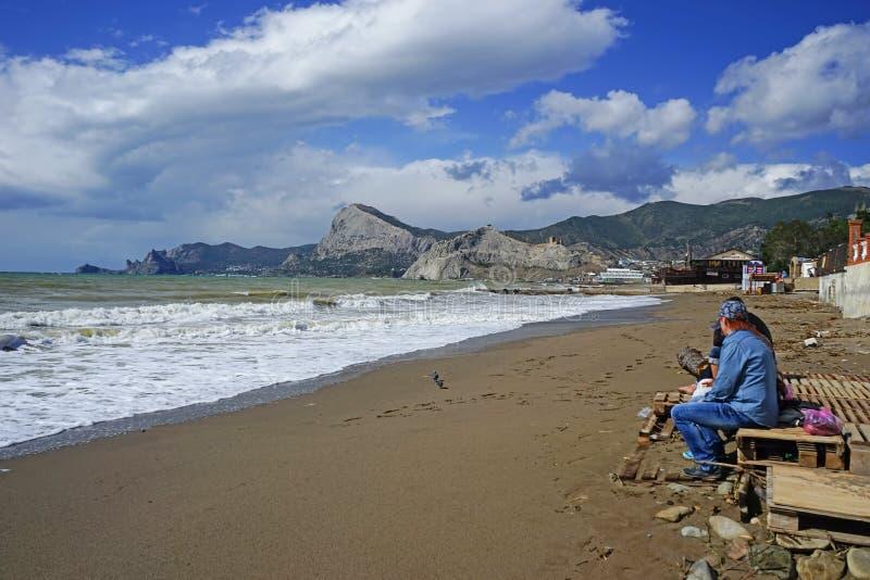 Leute entspannen sich auf dem Strand im Herbst lizenzfreies stockbild