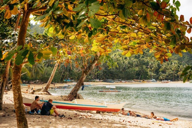 Leute entspannen sich auf tropischem Strand von Port-Barton stockfotografie