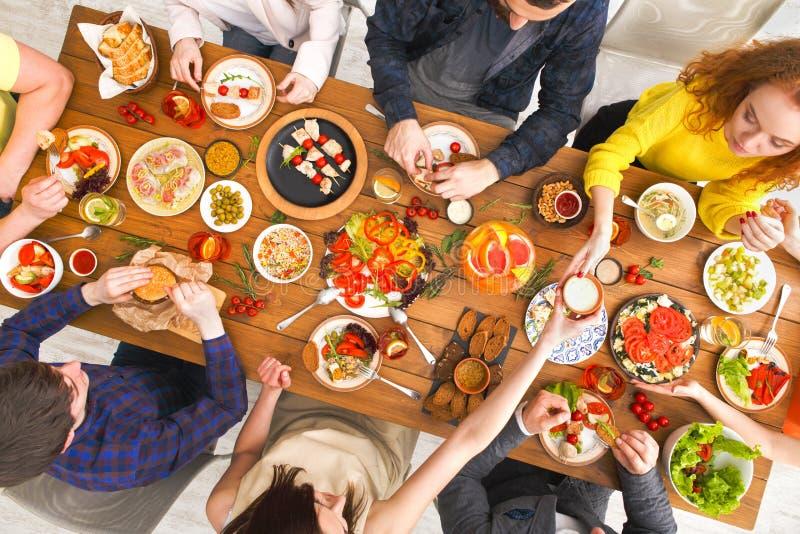 Leute essen gesunde Mahlzeiten an gedientem Tabellenabendessen lizenzfreie stockfotografie