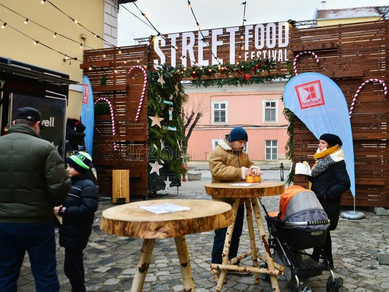 Leute essen Straßenlebensmittel an der Ausgabe des Straßen-Lebensmittel-Festivalwinters Verkäufer in den Lebensmittel-LKWs verkau lizenzfreies stockbild