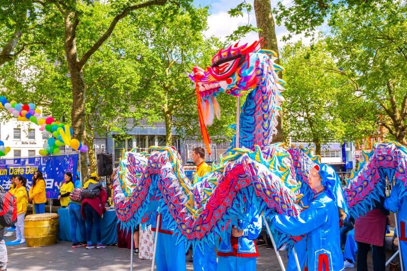 Leute führen Drachetanz für die Förderung der chinesischen religiösen Angelegenheiten Falun Gongs durch stockfotos
