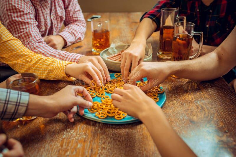 Leute, Freizeit, Freundschaft und Kommunikationskonzept - glückliche Freunde, welche die Bier-, Unterhaltungs- und Klirrengläser  lizenzfreie stockfotografie