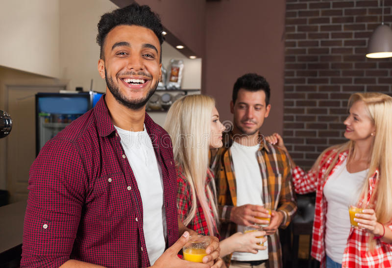 Leute-Freunde, die orange Juice Talking Laughing Sitting At-Bar-Zähler, Mischungs-Rennmann-glückliches Lächeln trinken stockbilder
