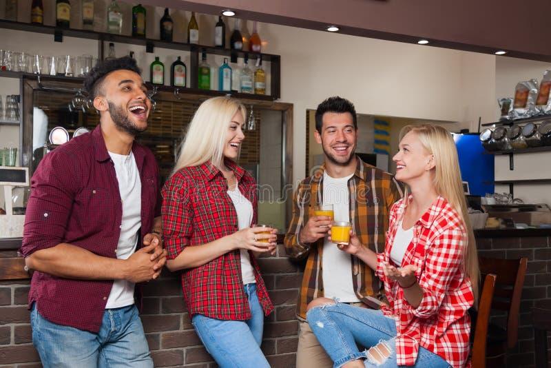 Leute-Freunde, die orange Juice Talking Laughing Sitting At-Bar-Zähler, Mischungs-Rennmann und Frauen-Paare trinken lizenzfreies stockbild