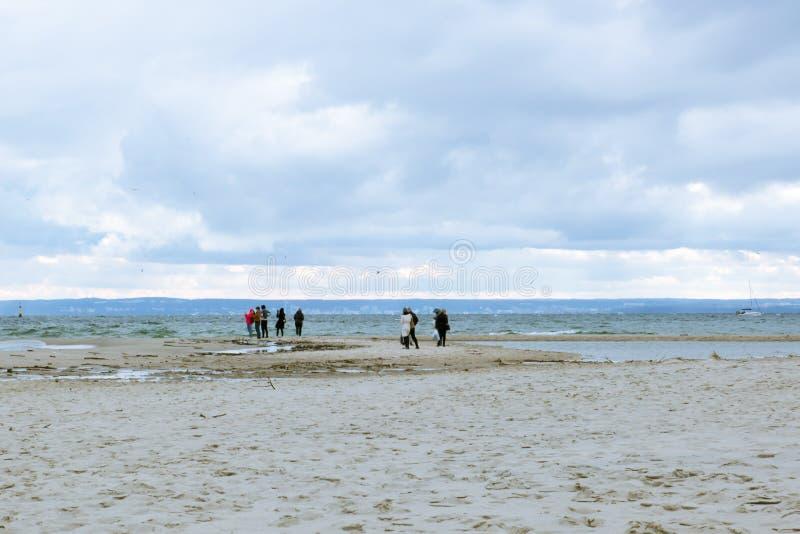 Leute gehen auf den Sand auf dem Seeufer lizenzfreies stockfoto