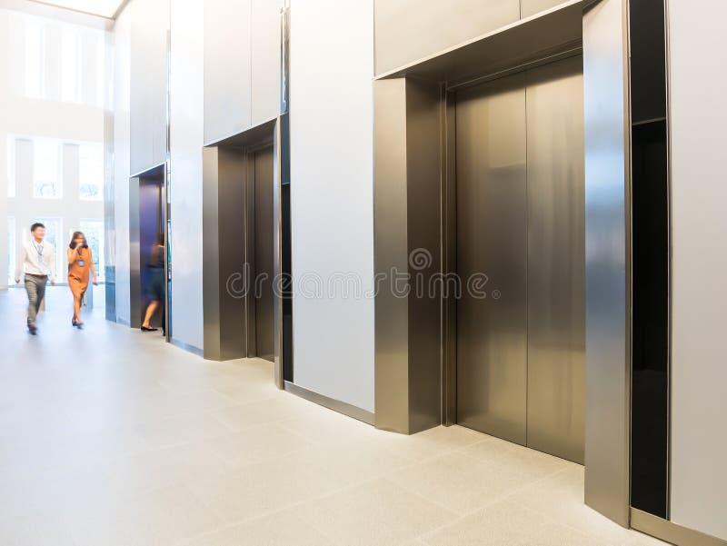 Leute gehen in Büro hinter Aufzügen, modernes Stahl-elevat stockfoto