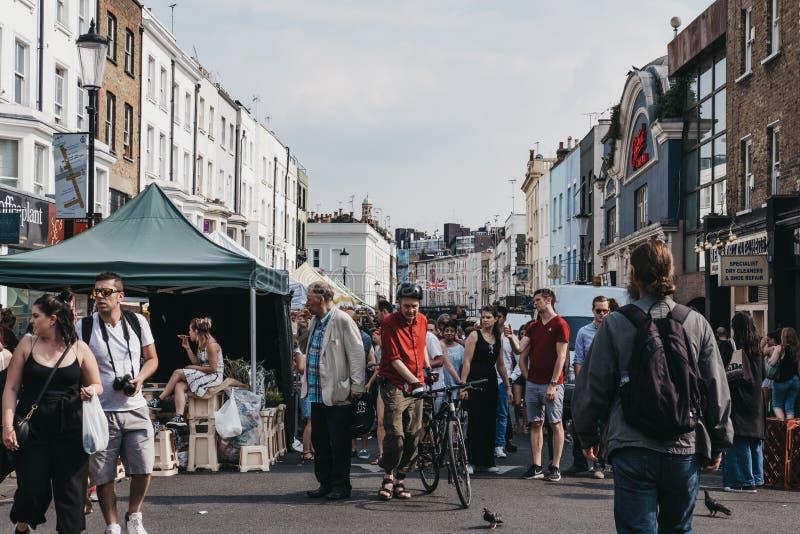 Leute gehen hinter Pastell-farbige Häuser auf Portobello-Straße Marke stockbilder