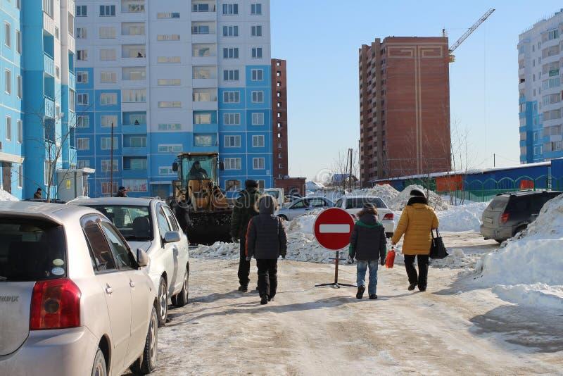 Leute gehen hinunter die Straße im Yard im Winter hinter den Autos sind ein Verbotszeichen stockfotos