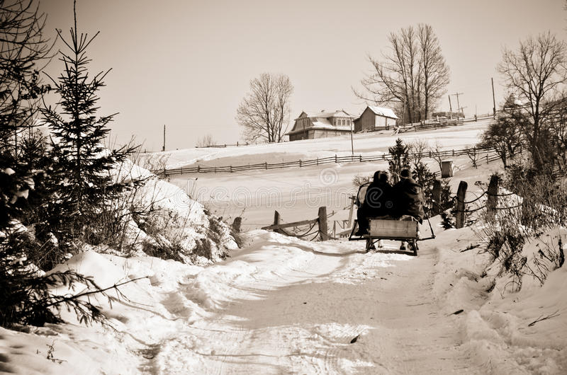 Leute gehen sledding, um auf Schneestraße am Berg im Winter automatisch anzusteuern lizenzfreies stockfoto