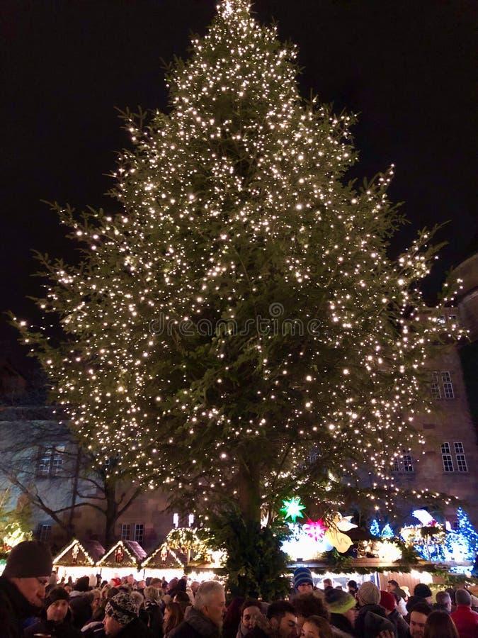 Leute genießen den Weihnachtsmarkt mit einem großen Weihnachtsbaum stockbild
