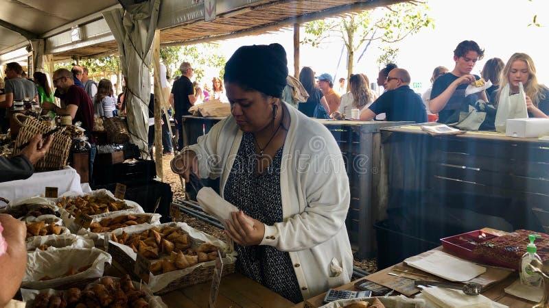 Leute genießen köstliche Nahrung an einem Neighbourgoods-Markt in der Ufergegend von Cape Town, Südafrika stockbild