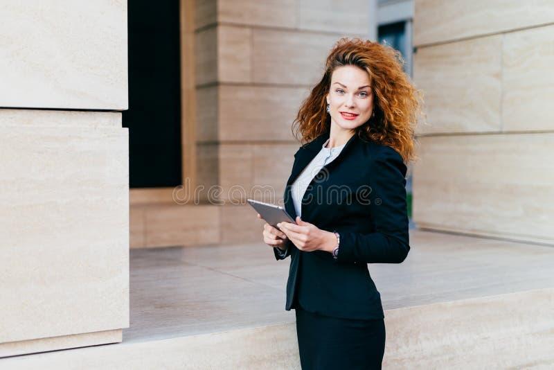 Leute, Geschäft, modernes Technologiekonzept Hübsche Geschäftsfrau, die schwarze Jacke und den Rock steht nahe ihrem Büro mit Umb stockbild