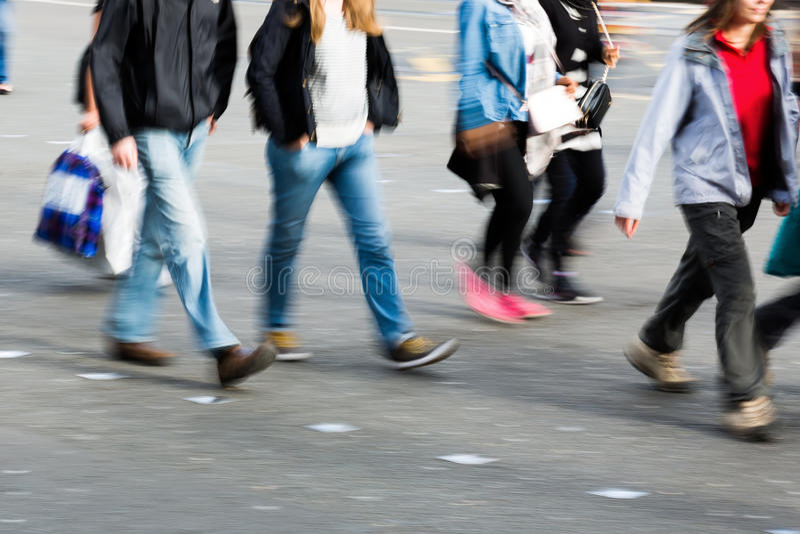 Leute gezeigt in der Bewegungsunschärfe, die eine Straße kreuzt stockfotografie