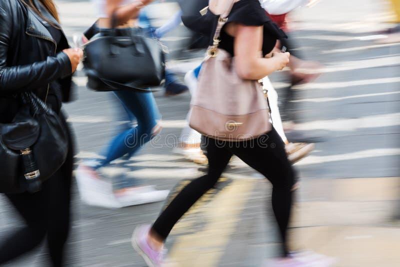 Leute gezeigt in der Bewegungsunschärfe, die eine Straße kreuzt lizenzfreie stockfotos