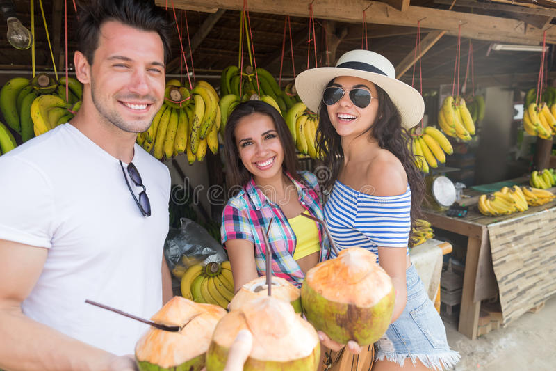 Leute-Gruppen-Getränk-Kokosnuss-Cocktail-Asiats-Frucht-Straßenmarkt-, das neues Lebensmittel, junge Freund-Touristen-exotische Fe lizenzfreie stockbilder