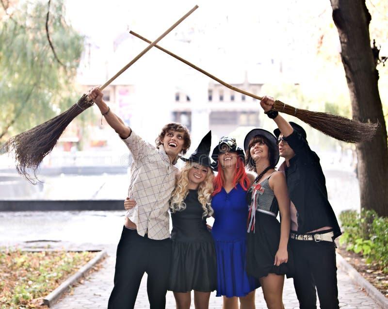 Leute gruppieren mit Besen, Halloween-Hexekostüm lizenzfreie stockfotografie