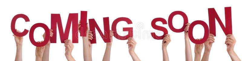 Leute-Hände, die das rote Wort bald kommt halten lizenzfreie stockfotos