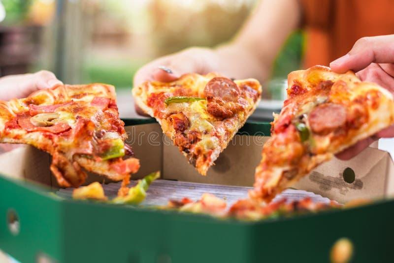 Leute-H?nde, die Scheiben der Pizza Margherita nehmen Pizza Margarita und H?nde schlie?en oben ?ber schwarzem Hintergrund lizenzfreie stockbilder