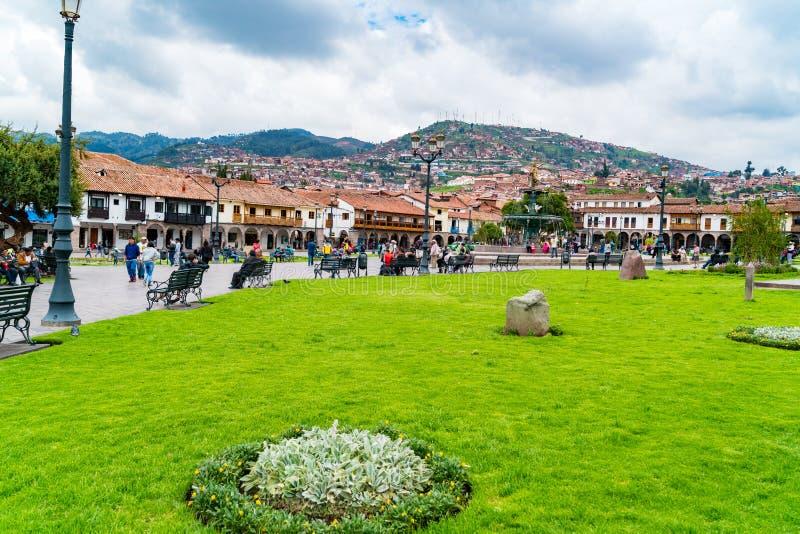 Leute am Hauptplatz Plaza de Armas mit der Statue von Pachacuti und Stadtbild von Cusco in Peru lizenzfreie stockfotografie