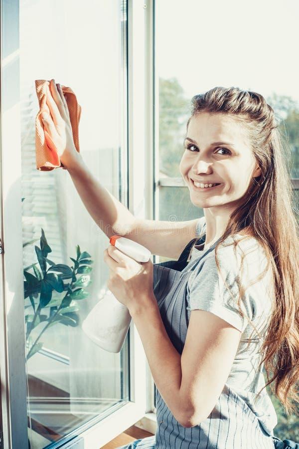 Leute-, Hausarbeit- und Haushaltungskonzept - glückliche Frau in den Handschuhen, die zu Hause Fenster mit Lappen- und Reinigersp lizenzfreie stockfotos