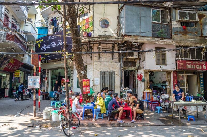 Leute können morgens gesehen, ihr Lebensmittel neben der Straße in Hanoi, Vietnam essend lizenzfreie stockfotos