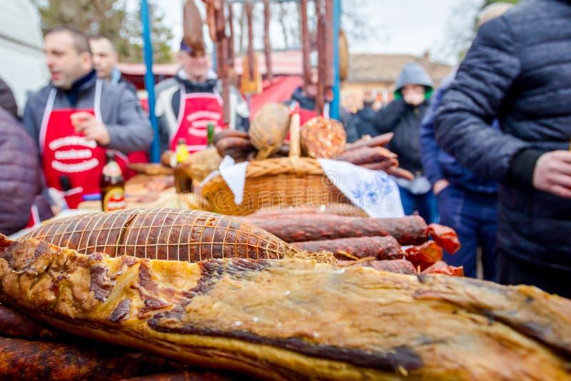 Leute kaufen geräuchertes Fleisch auf Stall, Straßenmarkt lizenzfreie stockfotos