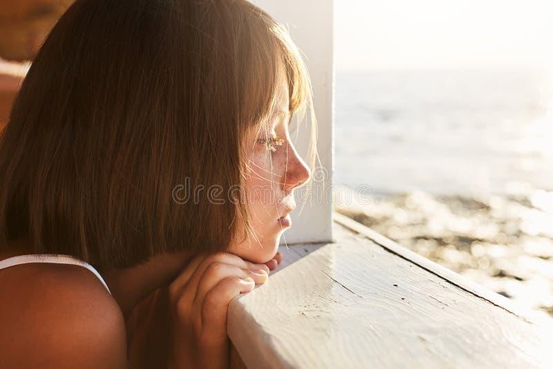Leute, Kinder, Entspannung, Stillekonzept Das entzückende Kind, das an der hölzernen Plattform, AR-Meer schauend sich lehnt, gest lizenzfreie stockbilder