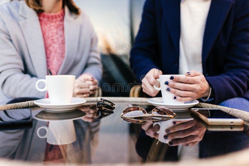 Leute-, Kommunikations- und Freundschaftskonzept - lächelnde junge Frauen, die Kaffee oder Tee trinken und Terrassencafé am im Fr lizenzfreie stockfotos