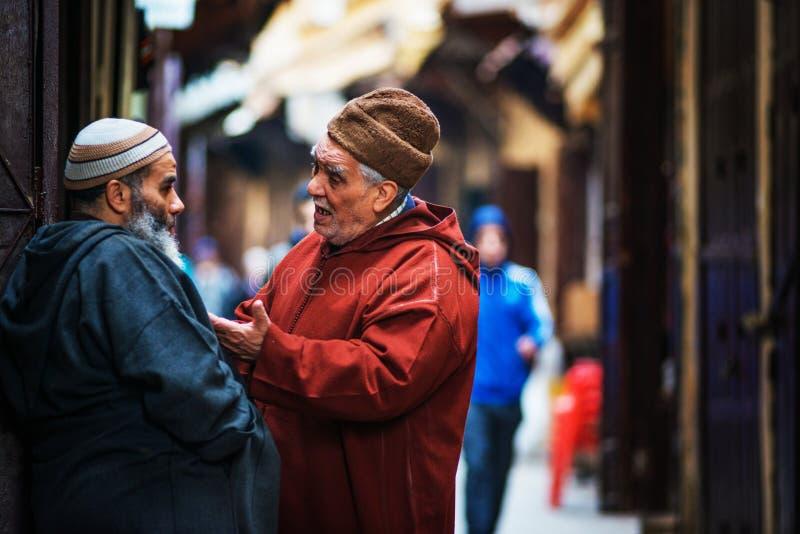 Leute-Manngespräch des Freunds älteres im alten Markt von Fes Medina mit traditionellem buntem Musselinkleid und Lebensstil, Fes, lizenzfreie stockfotografie