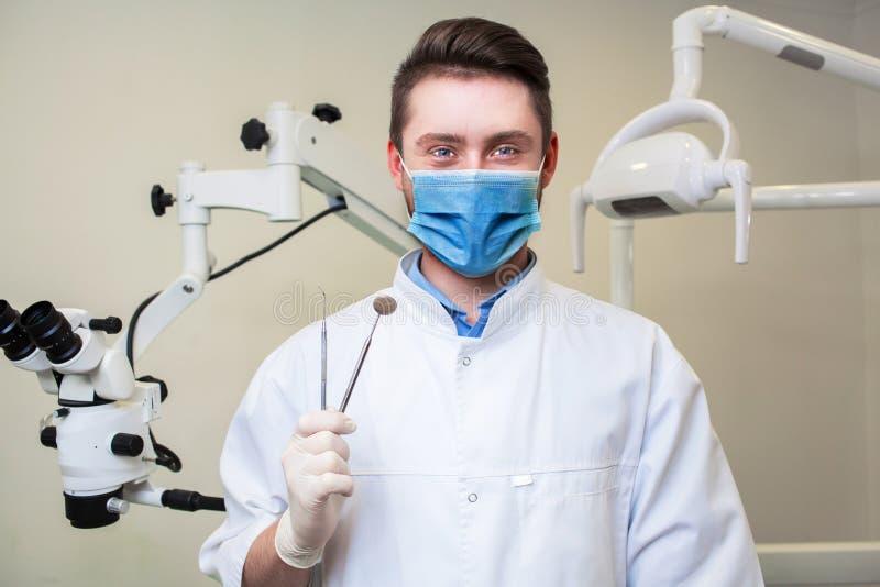 Leute-, Medizin-, Stomatologie- und Gesundheitswesenkonzept - glücklicher junger männlicher Zahnarzt mit Werkzeugen über Hintergr lizenzfreie stockfotos