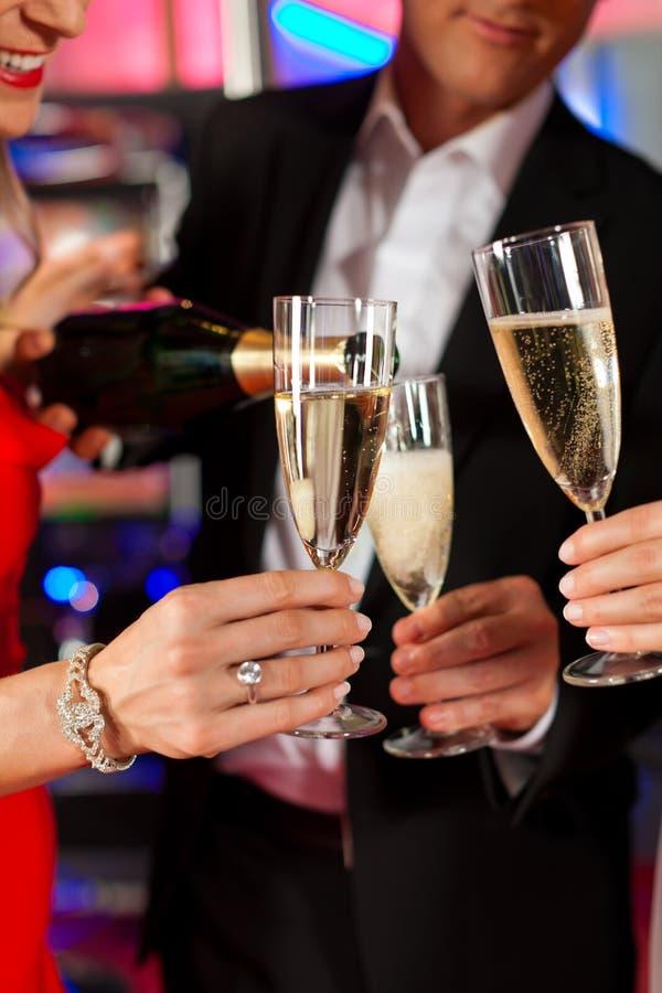 Leute mit champagner in einem Stab stockfotografie