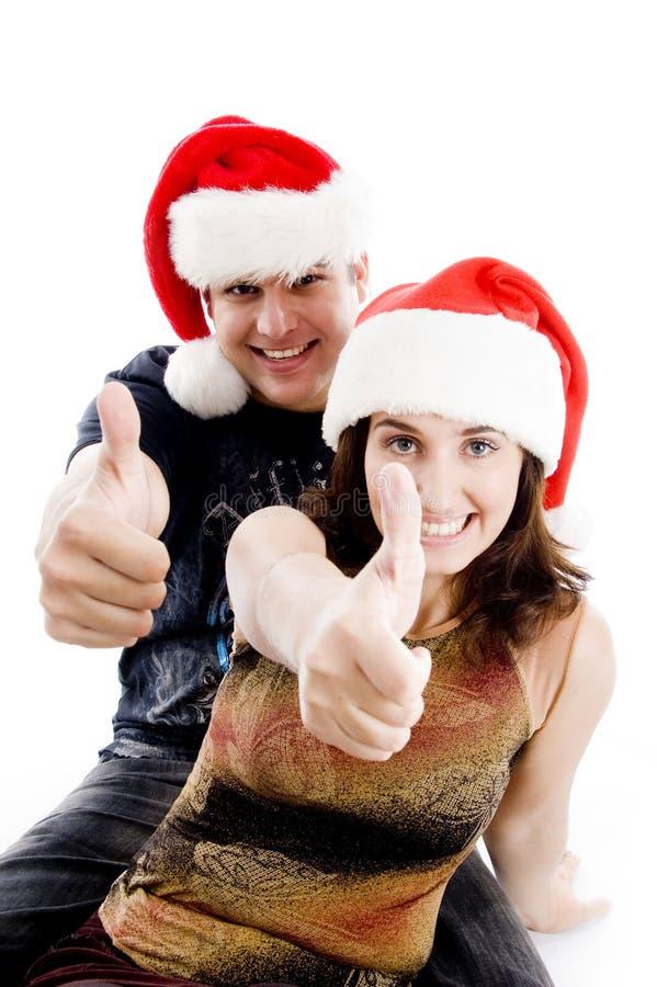 Leute mit dem Weihnachtshut, der sich Daumen zeigt stockfoto