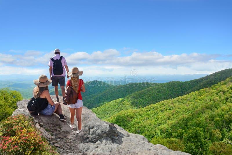 Leute mit den Rucksäcken, die auf Sommer wandern, lösen in den Bergen aus stockfotografie