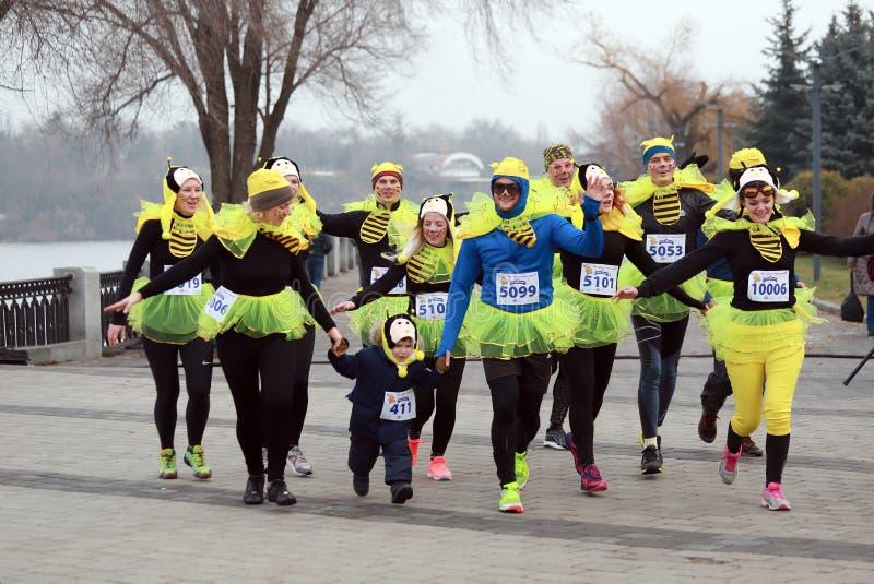 Leute mit einem kleinen Kind in Form eines lustigen Bienenlaufs auf Sportnächstenliebe Weihnachtsmarathon auf Dnepropetrovsk-Stra stockbilder