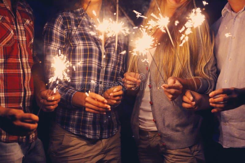 Leute mit Wunderkerzen auf Partei im Freien lizenzfreies stockbild