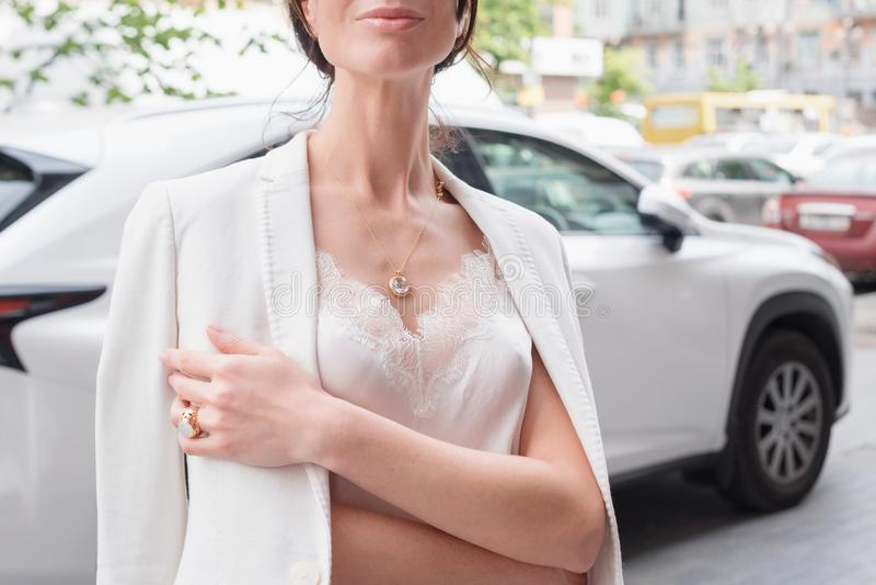 Leute, Mode, Schmuck und Luxuskonzept, Nahaufnahme der Frau den Luxusschmuck tragend, der nahe teurem Auto auf steht lizenzfreie stockfotografie