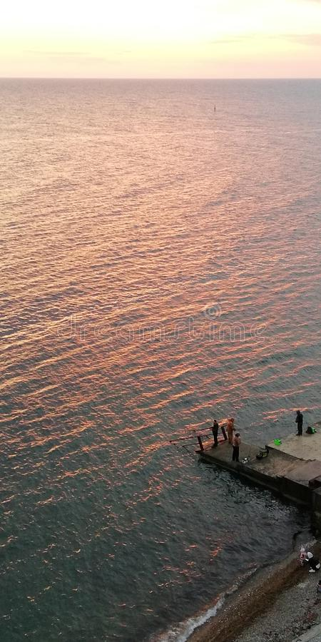 Leute nahe dem Meer auf einem felsigen Ufer Kalte Sonnenunterganglandschaft des Herbstes Hintergrund lizenzfreie stockfotografie