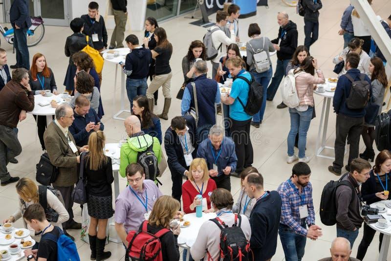 Leute nehmen Brötchen mit Rosinen auf einer Kaffeepause bei einer Konferenz stockfotografie