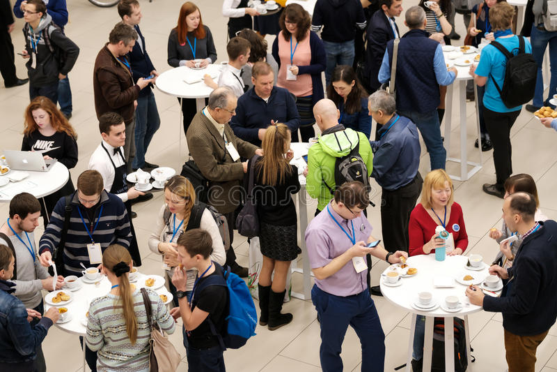 Leute nehmen Brötchen mit Rosinen auf einer Kaffeepause bei einer Konferenz lizenzfreie stockbilder