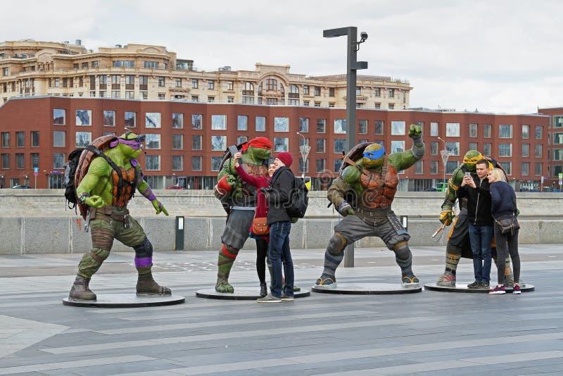 Leute nehmen ein selfie mit Telefon auf einem Hintergrund von Jugendmutant ninja Schildkrötenzahlen im Park Muzeon in Moskau stockbild